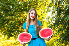 Beautiful young woman holding two halfs of watermelon Royalty Free Stock Photo