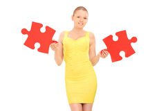 Beautiful young woman holding two pieces of puzzle Royalty Free Stock Photo