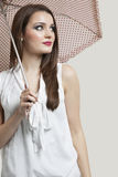 Beautiful young woman holding umbrella while looking away over gray background Stock Photo