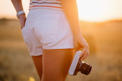 Beautiful young woman holding a vintage camera at hip level. Close-up, in the field at sunset Royalty Free Stock Photography