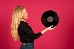 Beautiful young woman holding a vinyl in her hands as she listen. S to the music stock images
