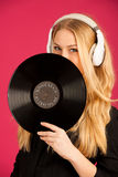Beautiful young woman holding a vinyl in her hands as she listen Royalty Free Stock Image