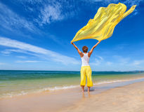 Beautiful young woman holding yellow fabric on wind. At the sea beach Royalty Free Stock Photography