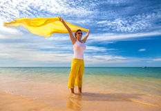 Beautiful young woman holding yellow fabric on wind. At the sea beach Royalty Free Stock Image
