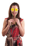 Beautiful young woman holds daffodils and covers her eyes with t Royalty Free Stock Images