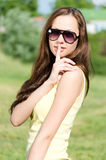 Beautiful young woman holds a finger to her lips in token of silence. Portrait. Park Stock Images