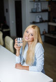 Beautiful young woman holds a glass with water Stock Photo