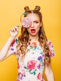 Beautiful young woman holds in hand candy Royalty Free Stock Image