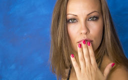 A beautiful young woman holds a hand near the mouth. Portrait. Blue background. Light brown hair. On the red nail polish. Glamorous. Fashion Royalty Free Stock Photo