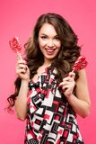 Beautiful young woman holds in hands candy smiling broadly. Stylish girl with bright makeup and candy in her hands royalty free stock photos