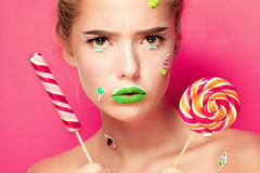 Beautiful young woman holds in hands candy smiling broadly. Stock Image