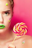 Beautiful young woman holds in hands candy smiling broadly. Stock Photo