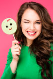 Beautiful young woman holds in hands candy smiling broadly. Stylish girl with bright makeup and  in her , isolated on pink backgro Stock Photo