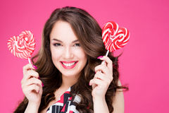 Beautiful young woman holds in hands candy smiling broadly.  Royalty Free Stock Photo