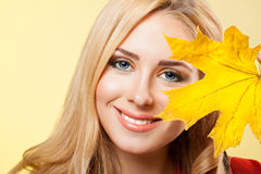 Beautiful young  woman holds maple leaf Royalty Free Stock Photo