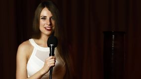 Beautiful young woman holds mic, looks at camera and sings with radiant smile
