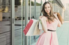 A beautiful young woman holds paper bags in her hands Stock Photos