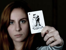 Beautiful young woman holds a playing card joker.  Stock Images