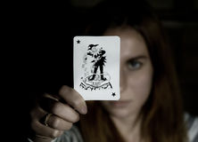 Beautiful young woman holds a playing card joker.  Stock Photography