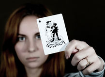 Beautiful young woman holds a playing card joker Stock Image