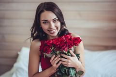 Young woman at home. Beautiful young woman at home. Attractive girl is sitting on bed with red roses in hands. Saint Valentines Day Royalty Free Stock Photo