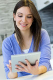 Beautiful young woman at home with digital tablet Royalty Free Stock Photos