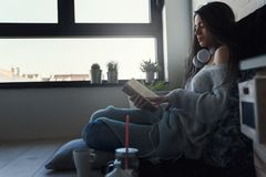 Beautiful young woman at home drinking coffee reading a book Stock Photography