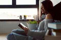 Beautiful young woman at home drinking coffee reading a book Royalty Free Stock Image