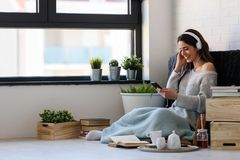 Beautiful young woman at home enjoys listening music Royalty Free Stock Image