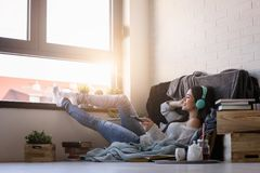 Beautiful young woman at home enjoys listening music through headphones royalty free stock photo