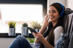 Beautiful young woman at home enjoys listening music through headphones stock images
