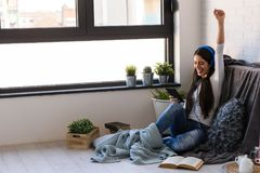 Beautiful young woman at home enjoys listening music. Portrait of beautiful young woman at home enjoys listening music in cozy corner by the window Royalty Free Stock Photos
