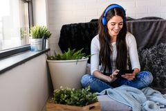Beautiful young woman at home enjoys listening music. Portrait of beautiful young woman at home enjoys listening music in cozy corner by the window Royalty Free Stock Image