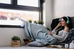 Beautiful young woman at home enjoys listening music. Portrait of beautiful young woman at home enjoys listening music in cozy corner by the window Stock Image