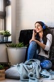 Beautiful young woman at home enjoys listening music. Portrait of beautiful young woman at home enjoys listening music in cozy corner by the window Stock Photo