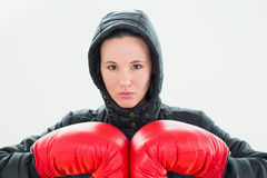 Beautiful young woman in hood and red boxing gloves Stock Photography