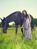 Beautiful young woman and horse. Photo of beautiful young woman and horse in summer field Royalty Free Stock Photography