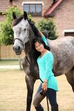 Beautiful young woman and horse near cottage Stock Photos