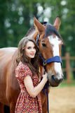 Beautiful young woman with a horse. Outdoor royalty free stock photo