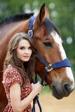 Beautiful young woman with a horse. Outdoor stock images