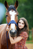 Beautiful young woman with a horse. Outdoor stock photos