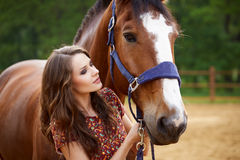 Beautiful young woman with a horse. Outdoor stock photography