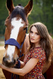 Beautiful young woman with a horse. Outdoor royalty free stock image