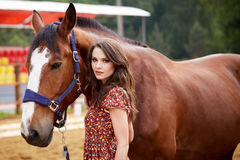 Beautiful young woman with a horse. Outdoor stock photo