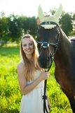 Beautiful young woman with horse outdoor on a walk in nature Royalty Free Stock Photo