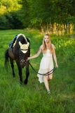 Beautiful young woman with horse outdoor on a walk in nature Stock Image