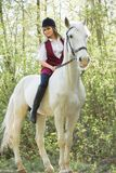 Brunette woman riding dark horse at summer green forest. Beautiful young woman on a horseback, outdoor portrait Royalty Free Stock Images