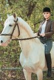 Brunette woman riding dark horse at summer green forest. Beautiful young woman on a horseback, outdoor portrait Royalty Free Stock Photo