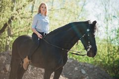 Brunette woman riding dark horse at summer green forest. Beautiful young woman on a horseback, outdoor portrait Stock Image