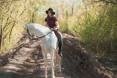 Brunette woman riding dark horse at summer green forest. Beautiful young woman on a horseback, outdoor portrait Stock Photography